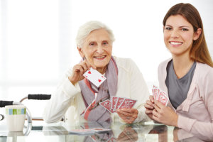 caregiver with her patient playing cards